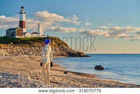 Woman tourist at the beach near Montauk Lighthouse, Long Island, New York, USA.