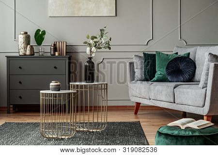 Two Stylish Small Coffee Tables With Marble Tops In Front Of Elegant Grey Couch With Emerald Pillows