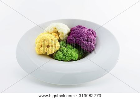 Concept Of Healthy Food. Four Colorful Raw Cauliflowers Served On A White Plate. Purple, White, Yell