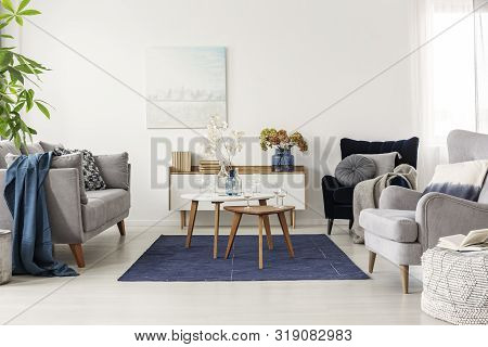 poster of Elegant white, grey and blue living room interior with scandinavian sofa and velvet armchair