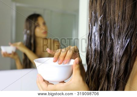 Hair Masking. Young Woman Hand Applying Natural Mask On Long Healthy Hair. Health And Beauty Concept