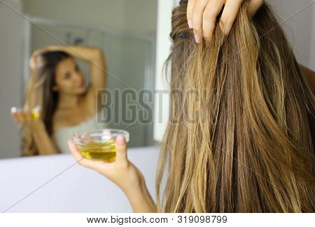 Young Woman Applying Olive Oil Mask On Hair In Front Of A Mirror. Hair Care Concept. Focus On Hair.