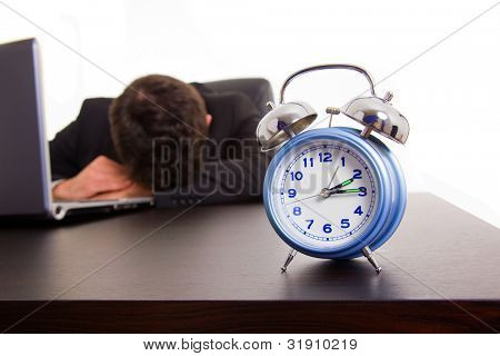 Exhausted young business man sleeping next to his laptop computer at the desk, isolated on white