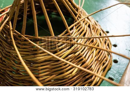 Unfinished Wickerwork Basket On Working Table. Handcraft Concept