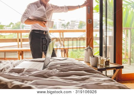 Open Laptop On The Bed With Businessman Stand Holding Coffee In Hotel Room