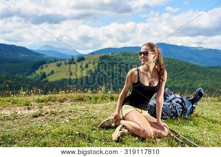 Attractive Happy Woman Hiker Hiking Mountain Trail, Resting On Grassy Hill With Trekking Sticks And