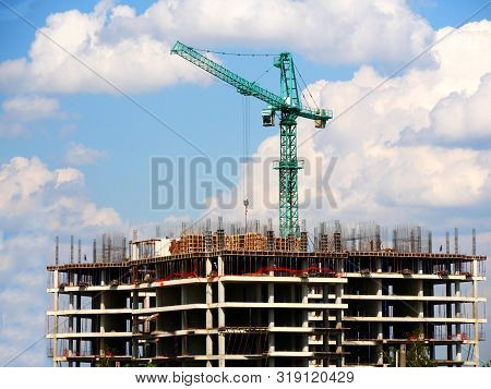 Concrete Building Under Construction. Construction Site. Crane Near Building. Industrial Background.