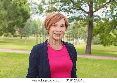 Healthy Senior Woman Walking In Park. Older Woman With Red Short Haircut Outdoors. Mature Beauty, 60