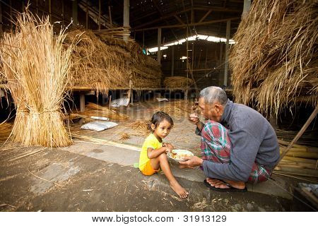 BALI, INDONESIA - APRIL 3: Unidentified poor child eats with his father during a break working on the farm  on Apr 3, 2012 on Bali. Daily caloric intake per capita in Indonesia is 2891 kcal per person