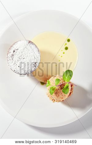Whole hot chocolate fondant with ice cream ball and condense milk on white plate isolated. Restaurant dessert with fresh brownie, muffin or small chocolate cake with crunchy rind and mellow filling poster