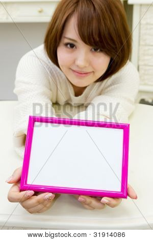 Beautiful young woman with message board