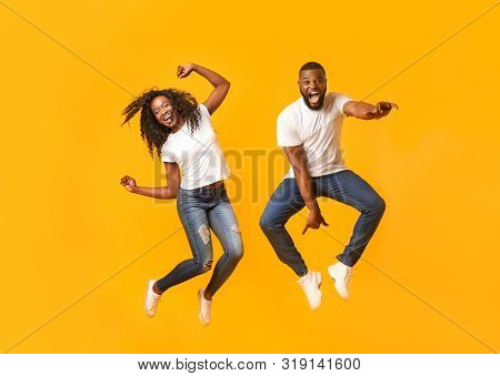 Super Excited Black Couple Leaping On Yellow Studio Background, Having Fun Together