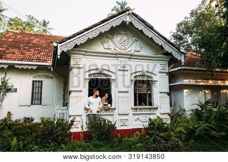 Couple In Love Drinking Tea At Home. Married Couple At The Window Of The House. Man And Woman In The