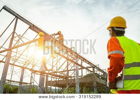 A Construction Worker Control In The Construction Of Roof Structures On Construction Site And Sunset