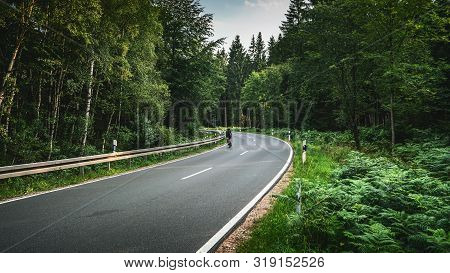 Bike On Long Curvy Forest Road In Alpine Mountains