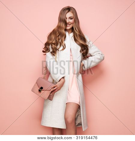 Young Elegant Woman In Trendy White Coat. Blond Hair, Pink Dress, Isolated Studio Shot. Fashion Autu