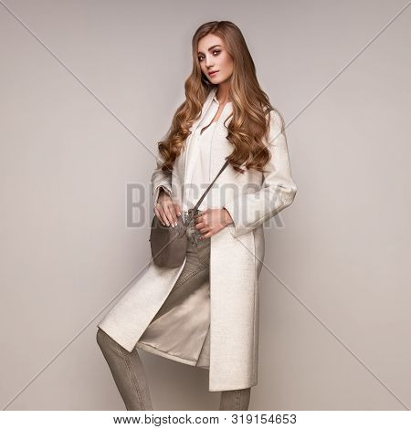 Young Elegant Woman In Trendy White Coat. Blond Hair, Gray Jeans, Isolated Studio Shot. Fashion Autu