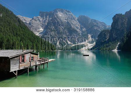 House With A Pier At A Mountain Lake Overlooking The Dolomites.