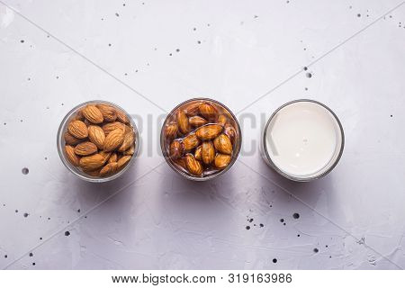 Making almond milk from dried almonds, a glass of soaked nuts and finished milk on a gray textured background. Top view poster