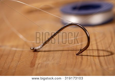 Large Classic Fishing Hook With A Thin Fishing Line Tied To It In A Reel On A Wooden Background