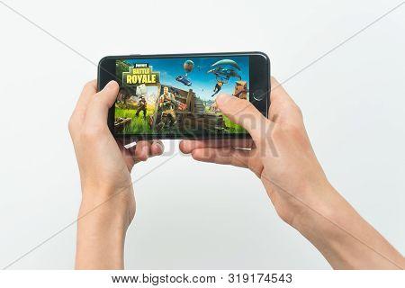 Samara, Russia -07, 29, 2019: A Young Guy Playing Fortnite Game On Iphone 8 Plus. Teenage Boy Holdin