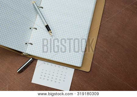 A Silver Fountain Pen, A Notebook With A Blue Cover And A Calendar Lie On A Wooden Table