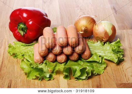 Fresh sousages and vegetables on wooden board