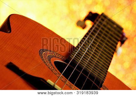 The Guitar Is A Stringed Plucked Musical Instrument, With Bokeh Lights In The Background. Guitar-acc