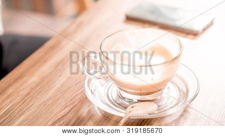 Coffee And Cafe Concept - Hot Latte Coffee Glass Cup On Wood Table With  Smartphone Background In Ca