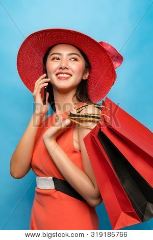 Beautiful Asian Girl Holding Shopping Bags Enjoy On Blue Color Background.portrait Of Young Beautifu