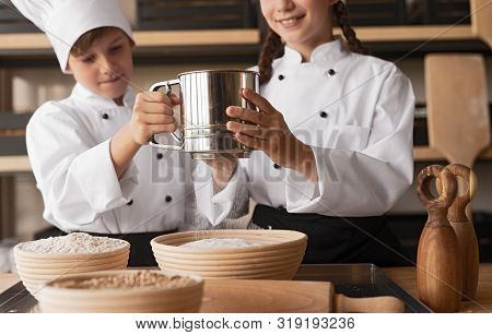 Diligent Kids In Chef Uniform Sifting Flour Into Wooden Bowl While Cooking Together At Rural Kitchen