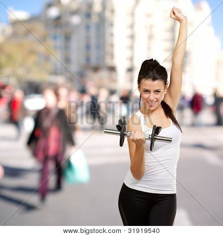 portrait of young woman doing fitness with weights at crowded street