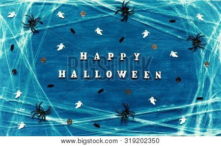 Halloween concept. Halloween festive background. Happy Halloween letters with spider web, spiders and Halloween decorations on the dark blue background