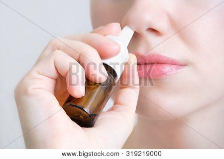 Nasal Spray.  Beautiful Young Woman. Closeup. Face With Nasal Drops. Close-up Of Female Spraying Med