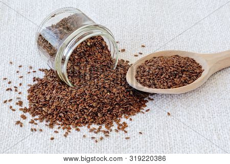 Fallen Glass Jar And Wooden Spoon With Whole Flax Seeds On A White Textile Table Mat. Healthy Food F