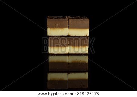 Group of four whole mellow two coloured nougat piece soft isolated on black glass poster