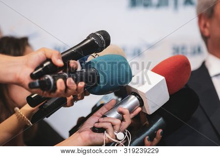 Details With The Hands Of Journalists Holding Worn Out Microphones In Front Of A Politician During A