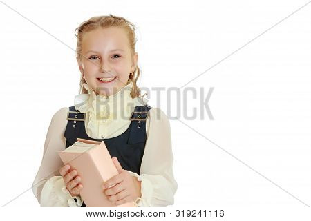 Dressy Girl Schoolgirl In Black Dress And White Blouse Holding A Textbook And Smiling Cheerfully At