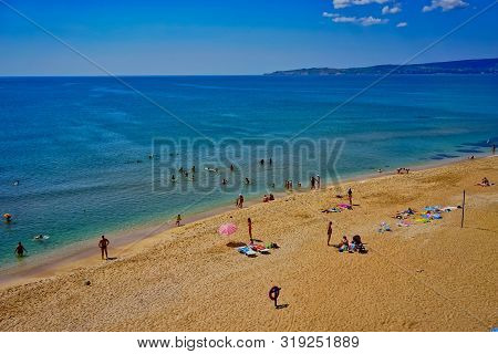 Feodosia, Crimea. Seascape With A Sandy Beach And Resting People In The Summer.