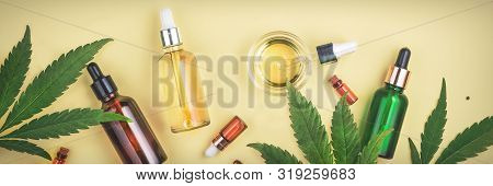 Different Glass Bottles With Cbd Oil, Thc Tincture And Cannabis Leaves On Yellow Background. Flat La