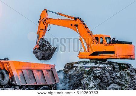 Excavator Is Loading Excavation To The Truck. Excavators Hydraulic Are Heavy Construction Equipment