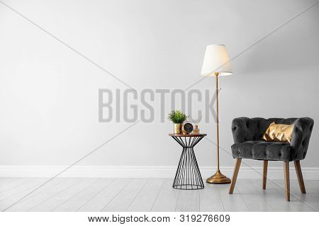 Stylish Room Interior With Comfortable Armchair, Floor Lamp Near Light Wall, Space For Text
