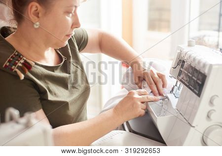 Clothier Sitting At Her Workplace And Sewing Fabrics On Professional Serger Sewing Machine. Close Up