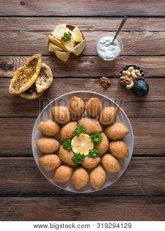 Delicious Fried Kibbeh With Yogurt Sauce In A Bowl Served On A Plate On Old Wooden Table. Classic Le
