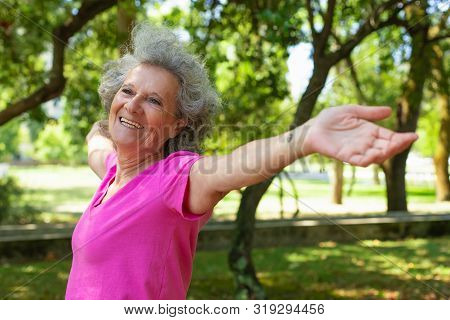 Positive Carefree Old Lady Enjoying Morning Exercise Outdoors. Senior Grey Haired Woman In Casual St