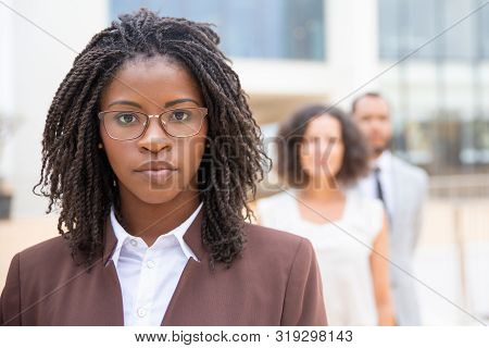 Serious Young African American Businesswoman. Portrait Of Confident Female Boss Standing With Collea