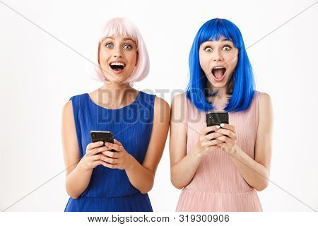 Portrait of two ecstatic women wearing blue and pink wigs looking at camera while typing on cellphones isolated over white background
