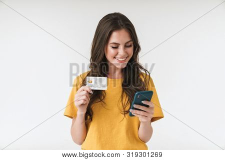 Image of gorgeous brunette woman wearing casual clothes holding credit card and cellphone isolated over white background