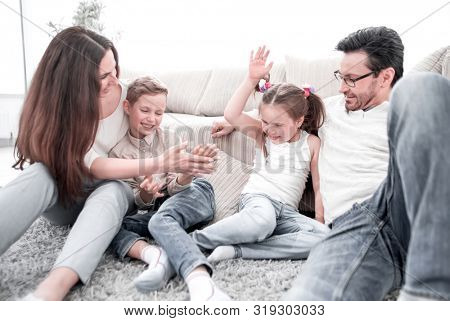 parents play with children sitting on the carpet in the living room