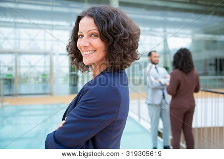 Confident Cheerful Businesswoman. Side View Of Professional Middle Aged Businesswoman Standing With